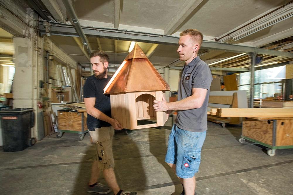 Mitarbeiter der Tischlerei Pickelein beim tragen eines kleinen Holzhäuschens