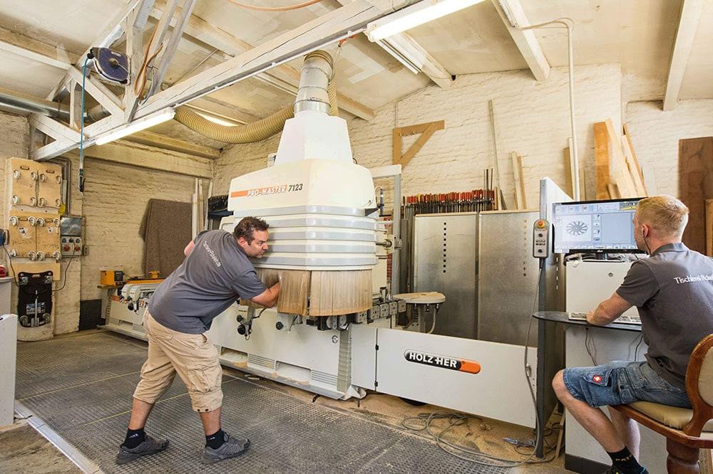 Zwei Mitarbeiter der Tischlerei Pickelein beim bedienen großer Maschinerie